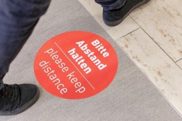 Die erforderlichen Schutzabstände werden durch ein Wegeleitsystem, Bodenmarkierungen, Hinweisschilder und mündliche Anweisungen sichergestellt.